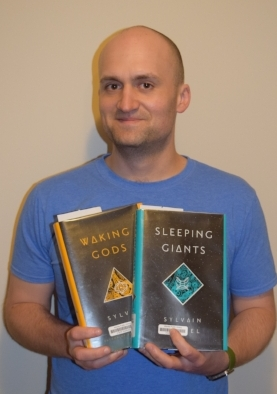 Adam, with his prodigious memory, is a big series fan and will even reread his favorites over and over. Here he's posing with his latest rereading project: Sleeping Giants by Sylvain Neuvel.