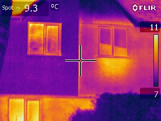 A picture taken with a Thermal Imaging camera. The house on the left has had external cladding, highlighting the loss of heat from the house on the right in the absence of sufficient insulation.