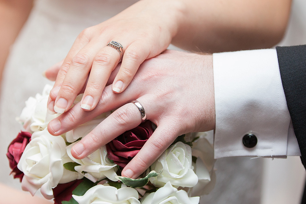 bride and groom holding hands with wedding rings.jpg