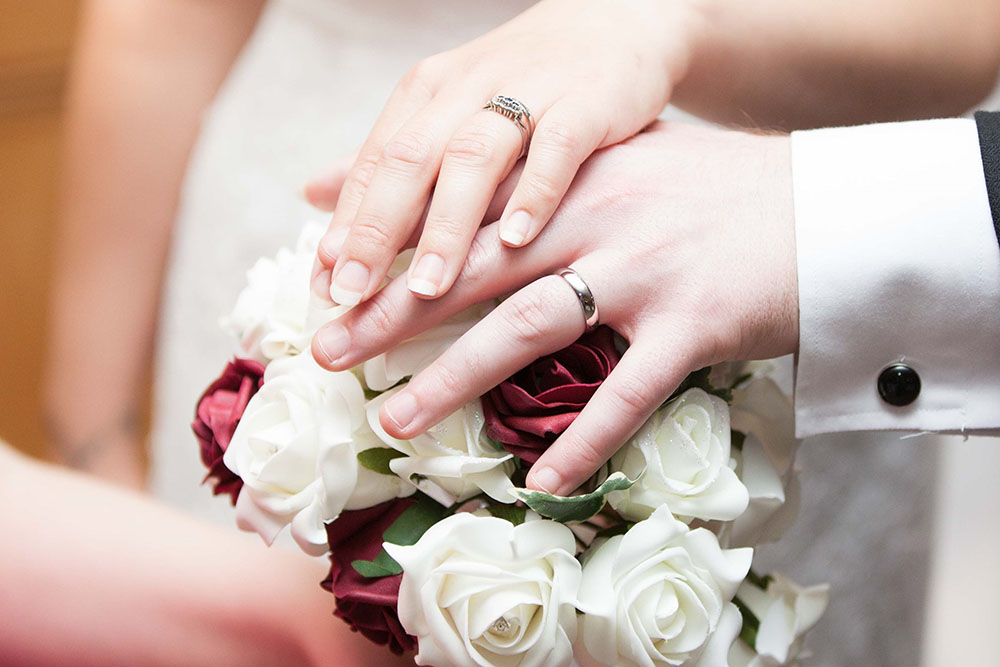 bride-and-groom-showing-wedding-rings-over-a-bouquet.jpg