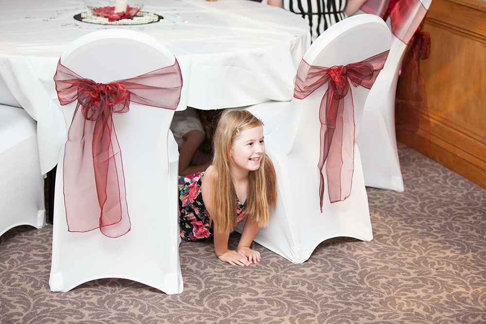 girl-in-dress-playing-under-tables.jpg