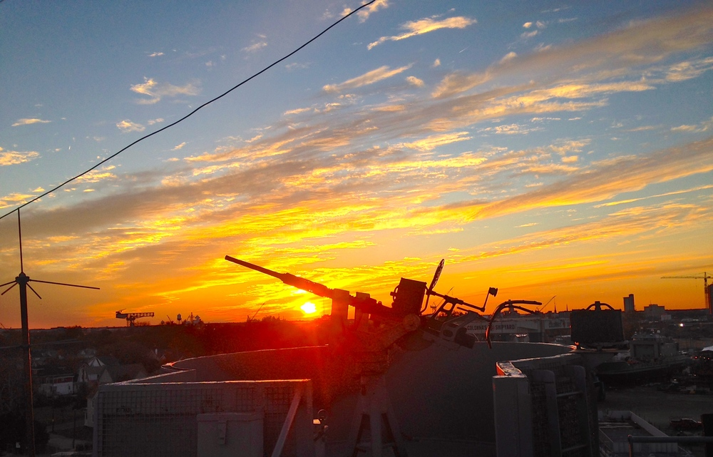 "The end of the day brings a regular ""debriefing"" with the crew including a great view of the sunset over Portsmouth and Norfolk VA. On the Horizon you can see the Hammerhead Crane used in the construction of American Battleships, which we will detail in a later post!"