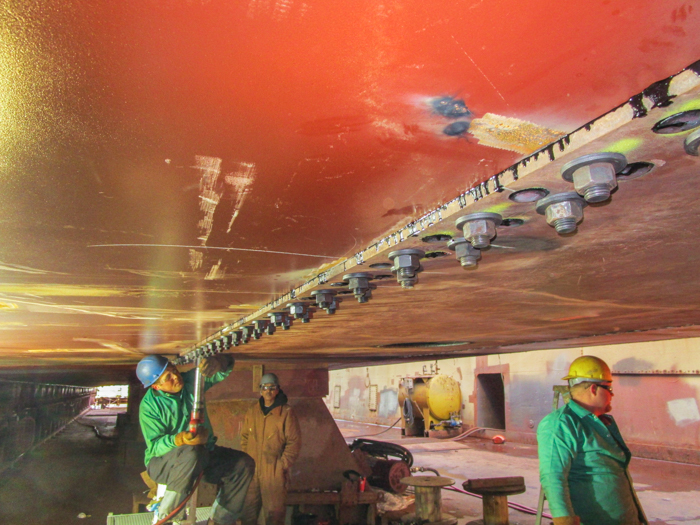 The two plates are initially bolted to hold them into place.  The riveters remove the bolts and replace them with rivets.