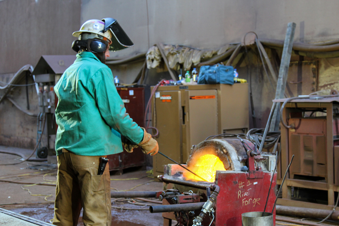The rivets are heated to over 2000 degrees Fahrenheit in a kerosene-fired forge.  This team member knows where the rest of team is in the process just by listening.