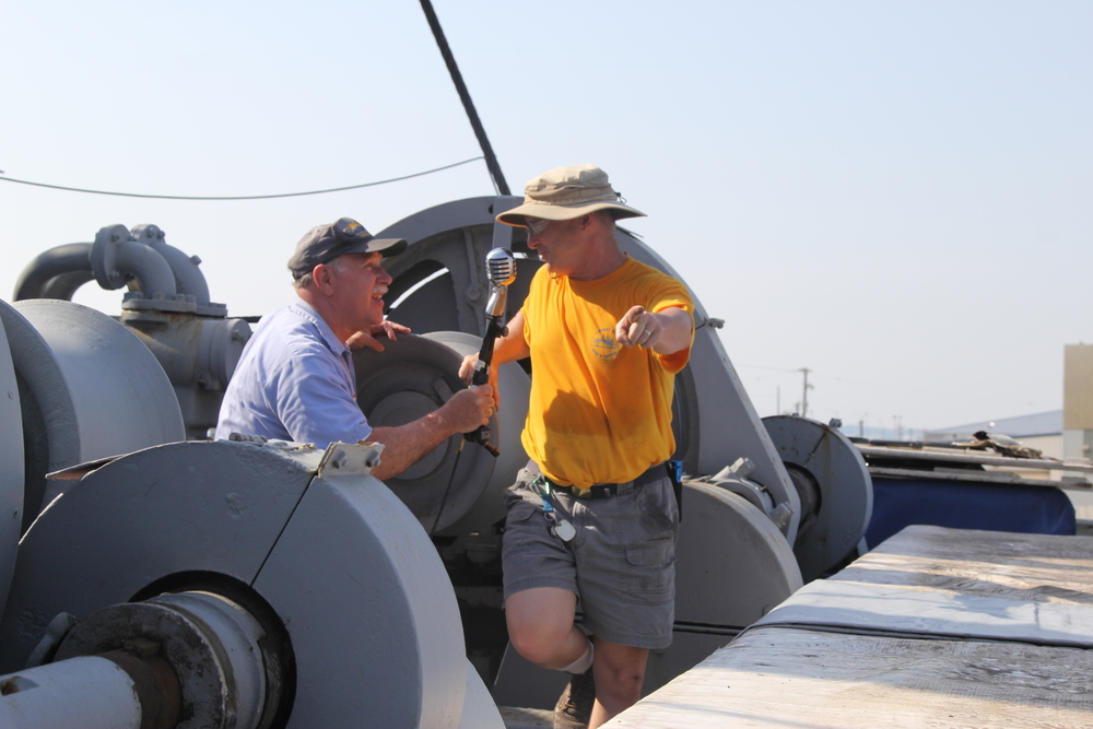 Howard directs Ray in microphone placement for the guest speakers before a cruise.