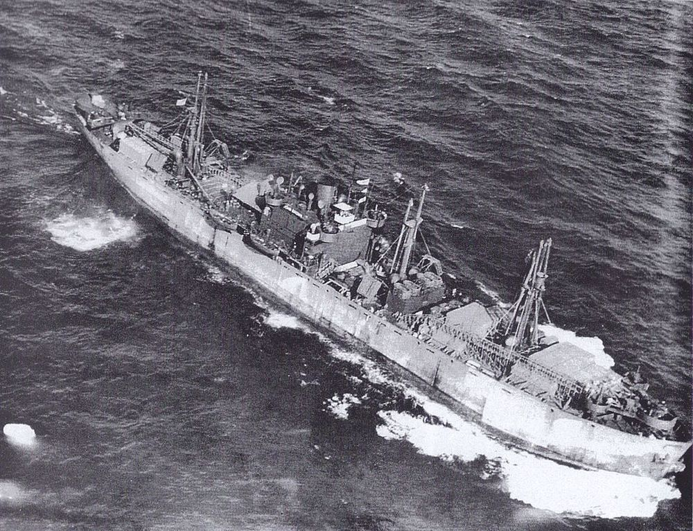 "This aerial photograph of the JOHN W BROWN outbound from the US carried a large deck cargo even after her conversion to a ""Limited Capacity Troopship."" This shot is most likely taken in the summer of 1943 during her second voyage. Notice how low in the water she is."