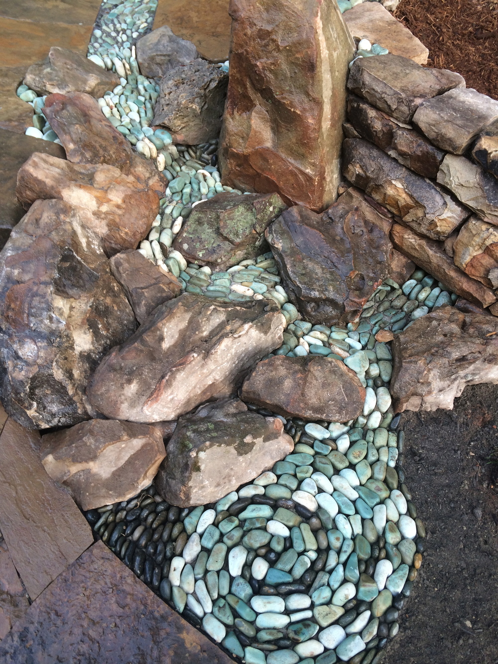 Dry stream winds through patio and falls through boulders