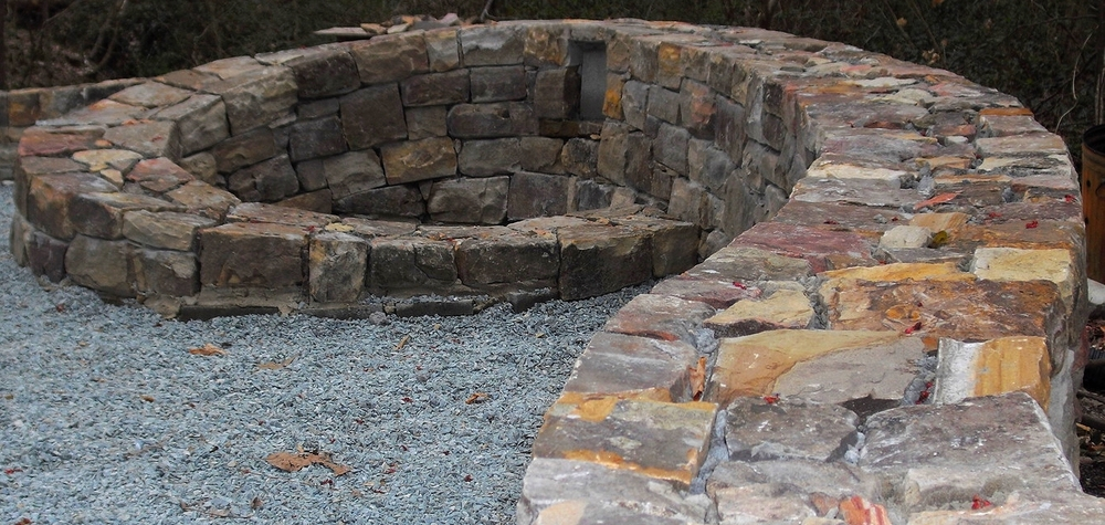 Curved building stone wall and fire pit not yet finished