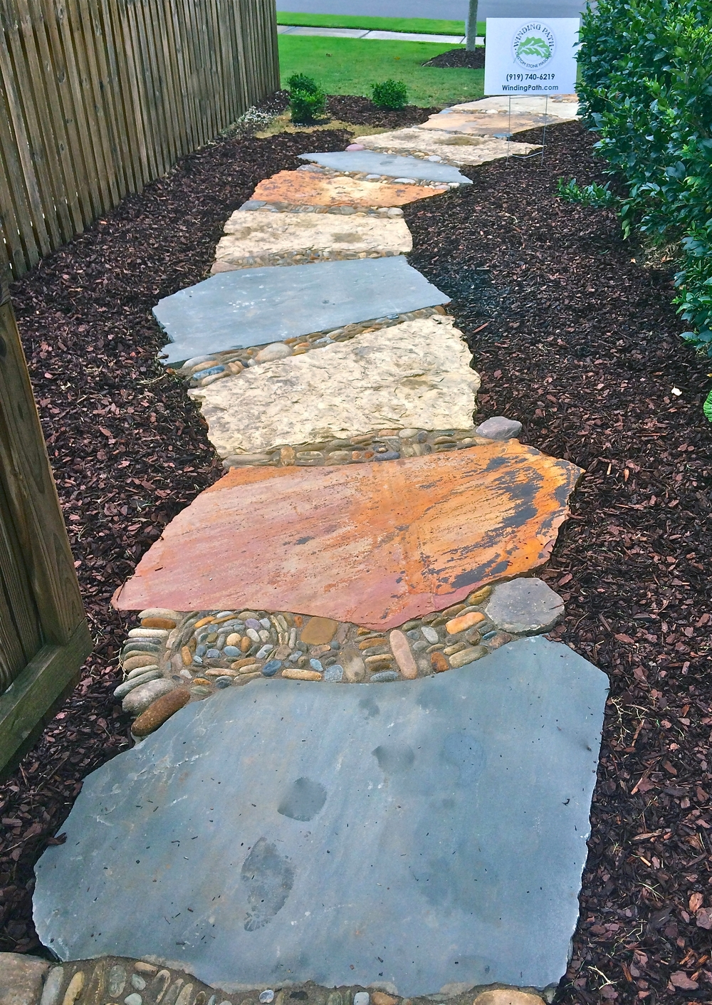 Thick flagstones with inlaid pebbles creates a winding garden path