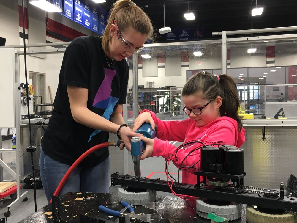 "On 148 we have a rule: "" Every Wrangler Rivets .""  Today this rule applies to everyone: including guests.  Here you can see Madison showing young Miss Freeman how to assemble a drivetrain.  (She ended up staying to help build for a few hours!)"