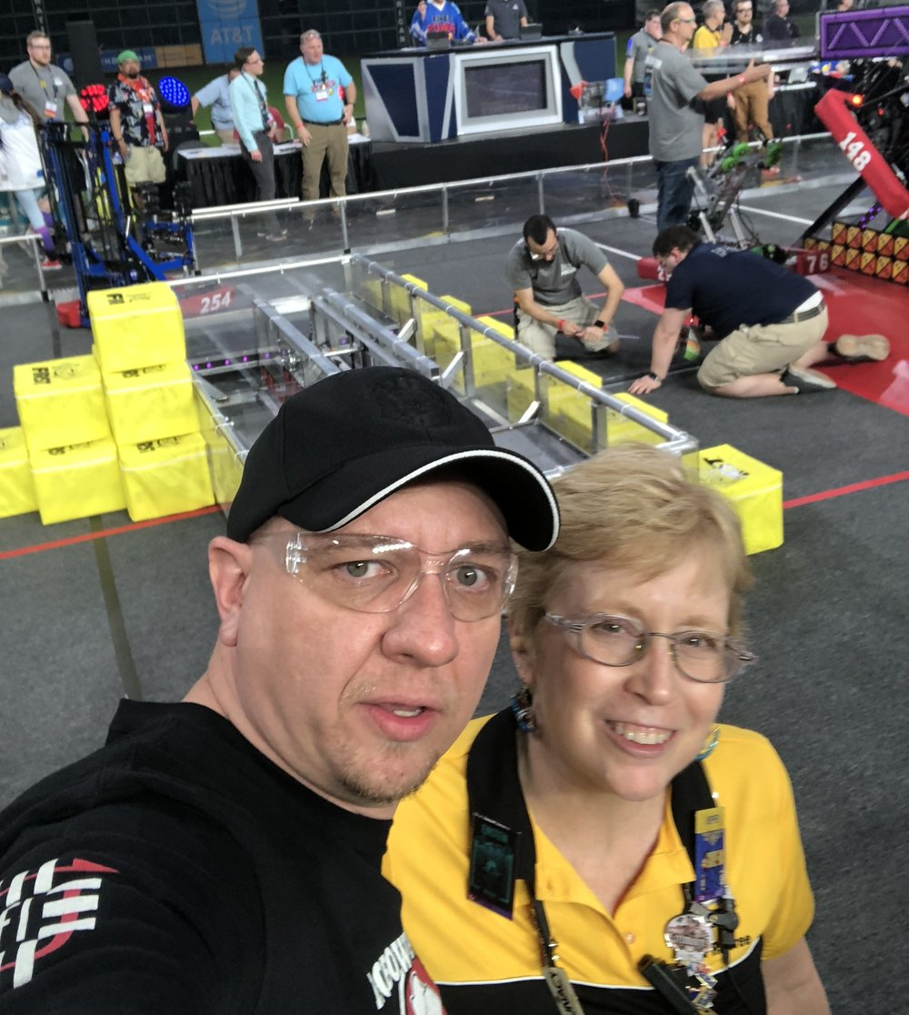 "This is Carol Perrotto. Carol has been a head-ref for years, and a friend of the Robowranglers for just as long. Carol won the FIRST Volunteer of the Year in Detroit  (Congrats Carol!)   In Minute Maid Park, one of Carol's jobs as a ref was to make sure no one from our alliance was stupid enough to walk onto the field before the field ""all clear"" signal and get a Red Card. She planted herself in the gate and actively blocked Coleman and I from trying to walk out there. We weren't planning on it... but we still had fun pretending to get past her."