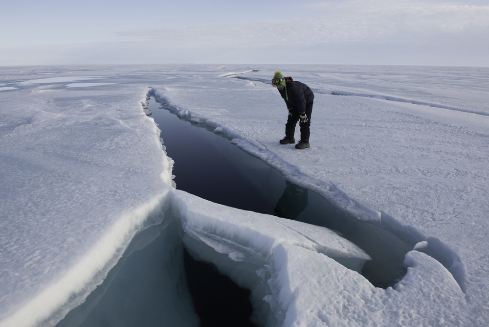 Kenneth Kaloon looks down a crack in the ice.