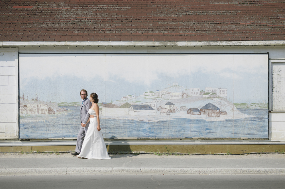 Kim and Devin Lake walk in front of a mural of Old Town, Yellowknife in Old Town, Yellowknife.