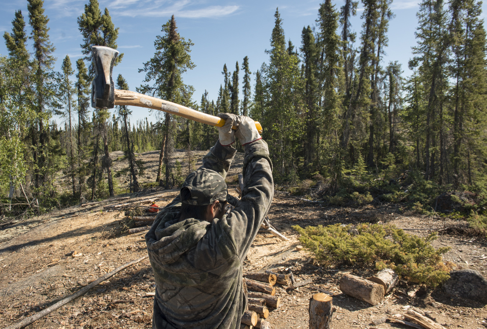Jonathan Konistea, a student from Nahanni Butte, NWT, chops fire wood.