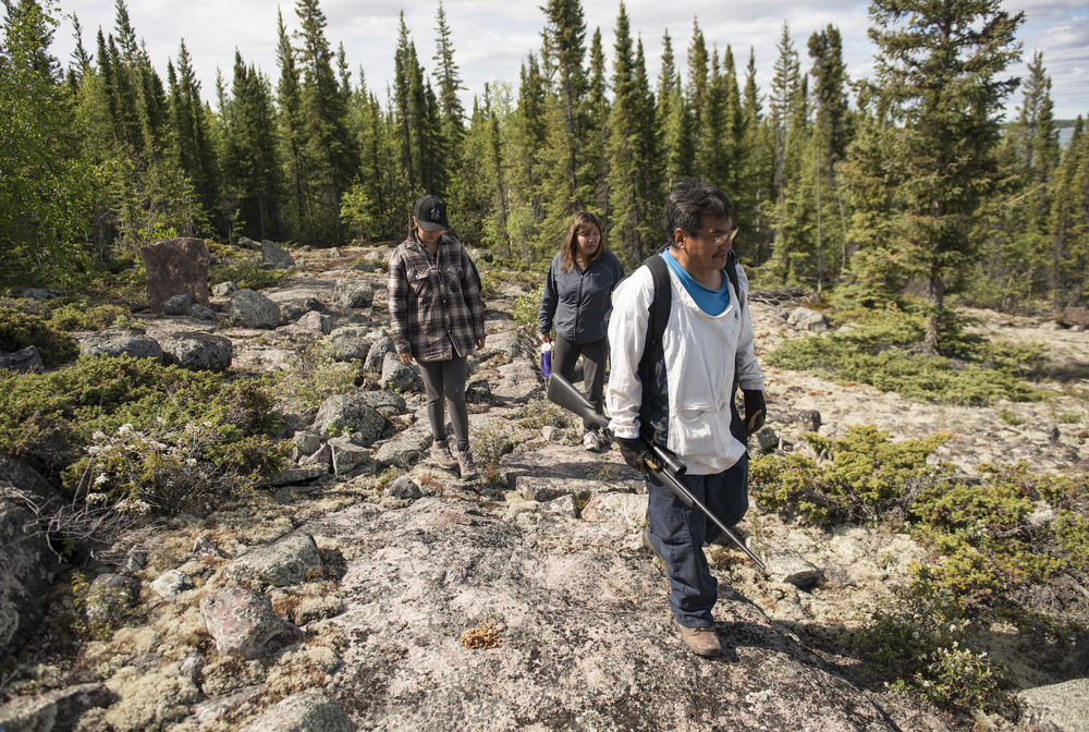 Archie Sangris leads Crystal Campbell and Joanne Krutko on a hike. Guns are needed because of the many black bears in the area.