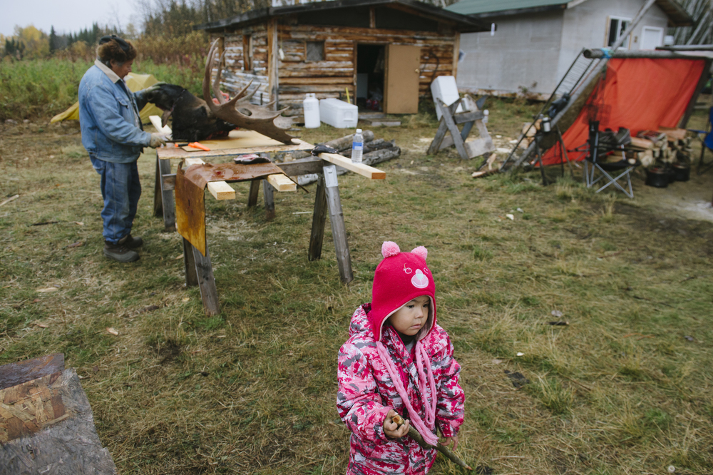 Leah Simba plays at a hunting camp at Tathlina Lake while her great grandfather, Gabe Chicot, inspects a moose head in the background. Photographed for On the Land/Tides Canada.