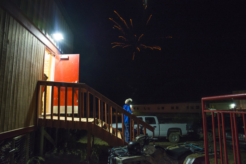 A boy takes a moment to watch the last fireworks go off while a drum dance takes place inside the community hall in Deline, NWT. This year Deline signed a self-government agreement in an historic step forward for indigenous communities in the Northwest Territories.