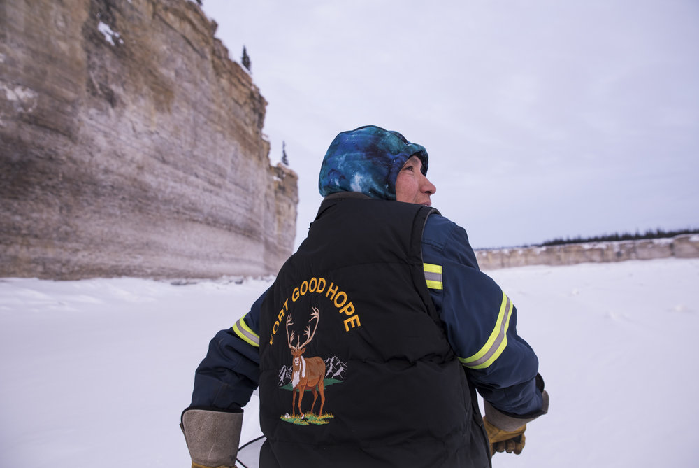 Buddy Gully drives his ski-do beside the Mackenzie River ramparts' limestone cliffs near Fort Good Hope, NWT. A Dene legend says that a hero named Yamoga saved many people after fighting a giant beaver. When he laid down to rest, his body formed the ramparts.