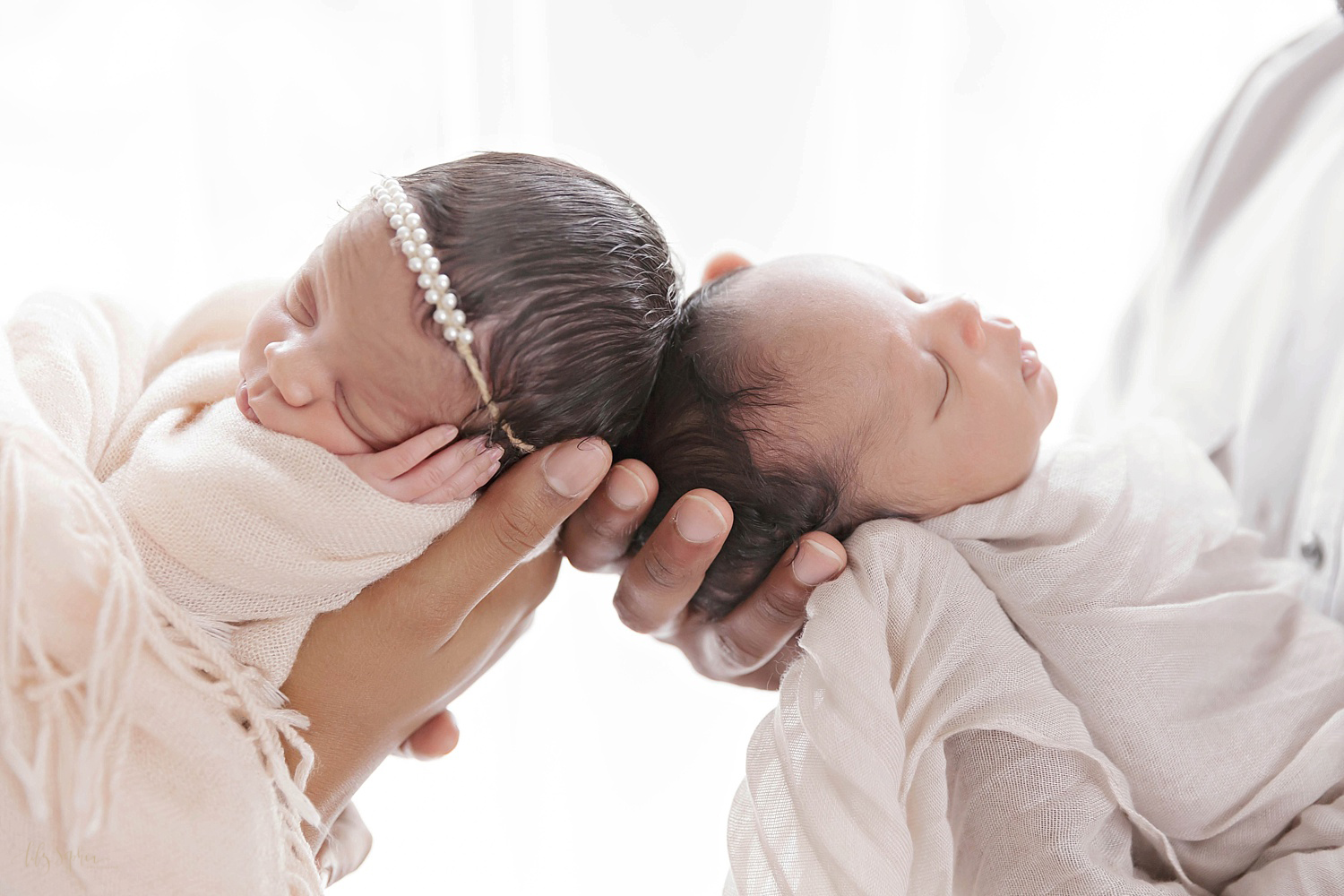 Image of sleeping african american newborn twins being held up head to head and