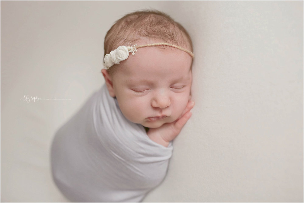 Image of sleeping newborn baby girl in atlanta natural light studio wrapped in lavender wrap with