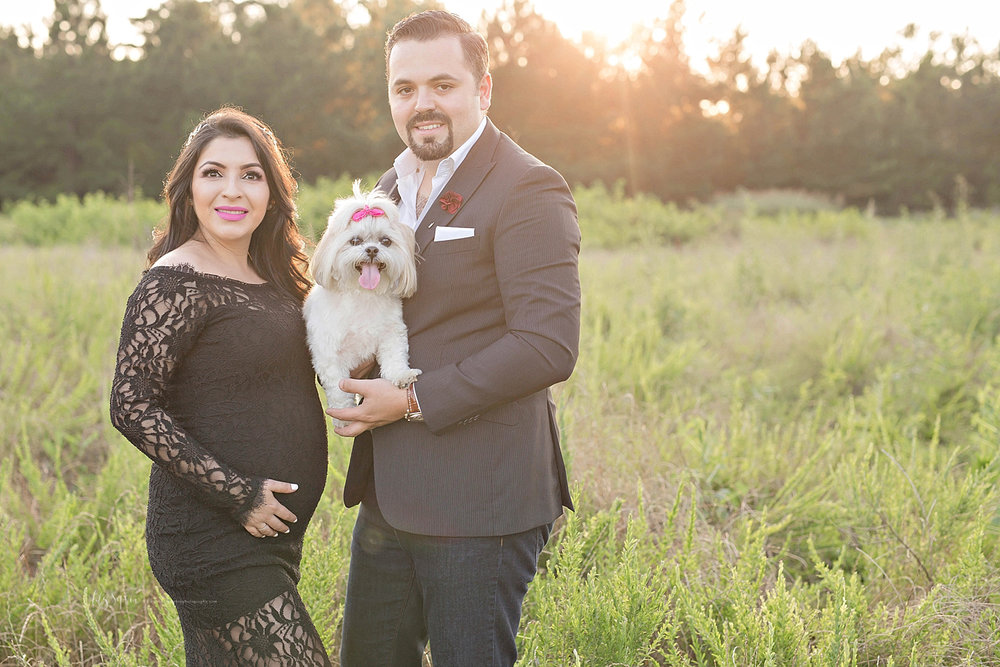 Image of a pregnant Latina woman, wearing a black lace dress, standing with her husband who is holding their little dog.