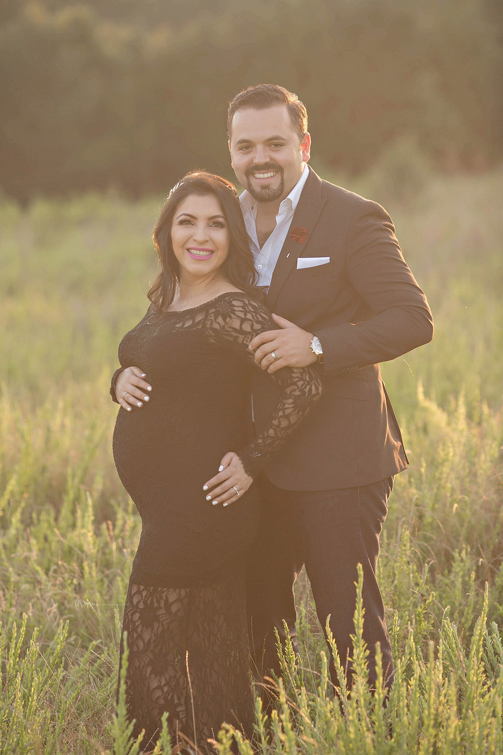 Image of a pregnant Latino couple, standing in a field at sunset, smiling.