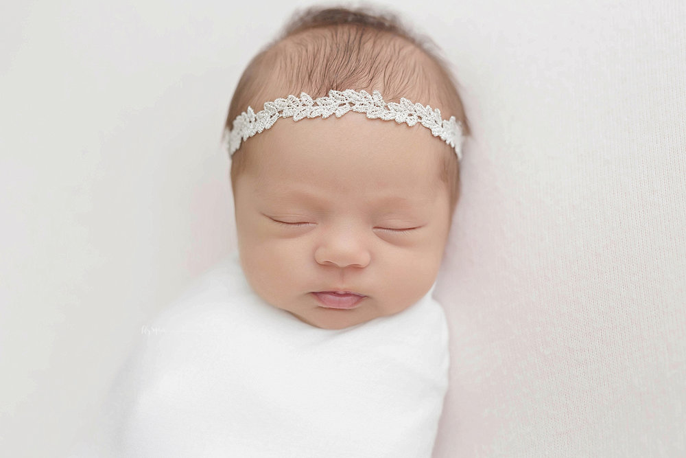 Image of a sleeping, newborn, baby girl, swaddled.