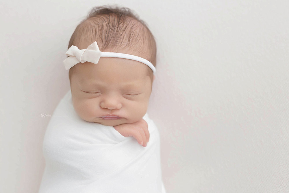 Image of a sleeping, newborn, girl with a bow tieback, swaddled, with one hand peeking out.