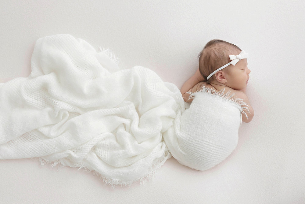 Image of a sleeping, newborn, baby, girl, on her belly, with her hands tucked under her.