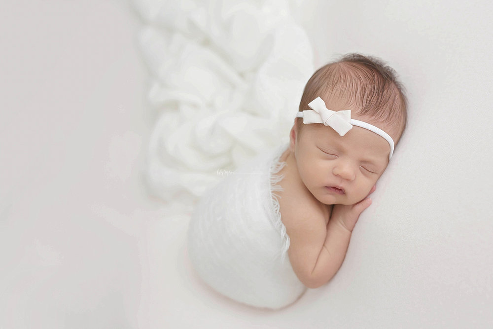 Image of a sleeping, newborn, baby, girl, with a bow in her hair, with her hand tucked under her chin.