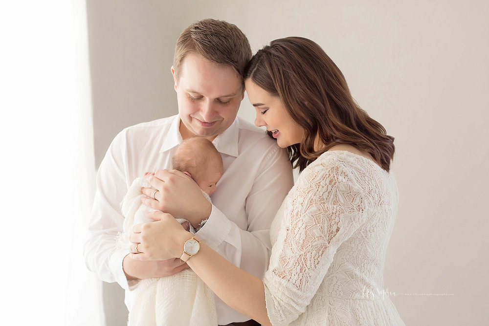 Image of a father, cradling his newborn son to his chest, while his wife looks down at the baby, and smiles.