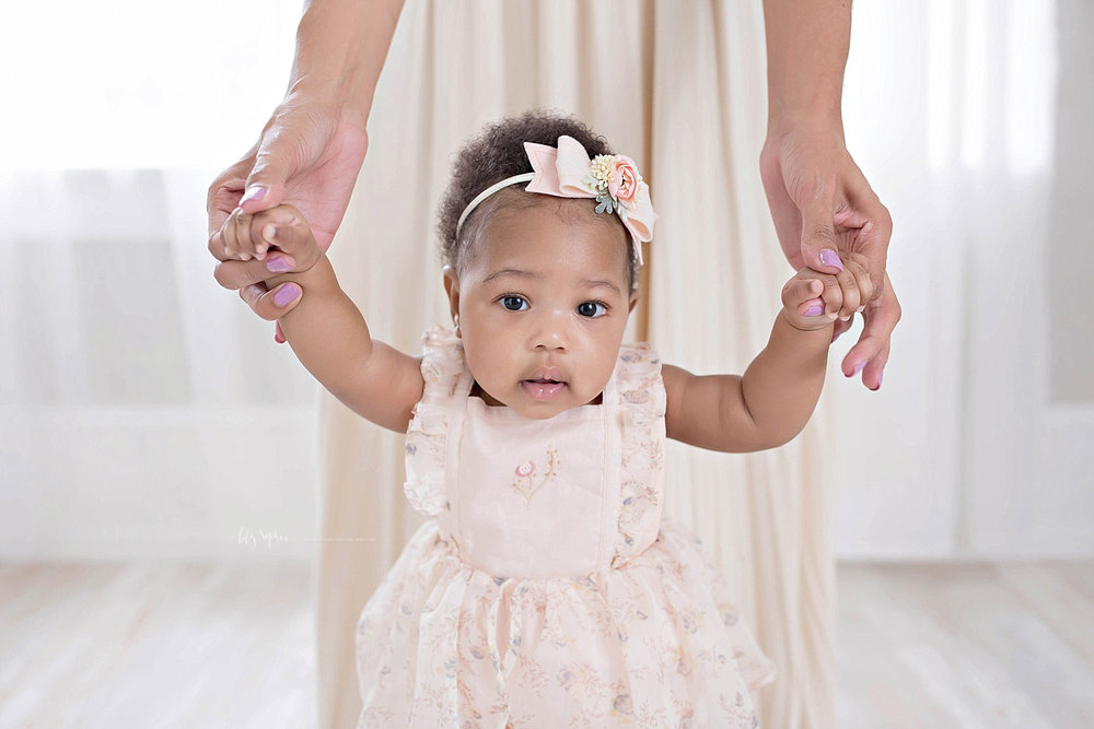 Image of a African American, baby, girl, standing up with the help of her mother.