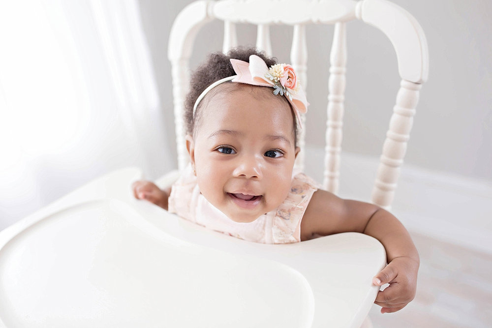 Image of a smiling, African American, toddler girl, with a pink, flower, bow headband in her hair, sitting in an antique wooden highchair.