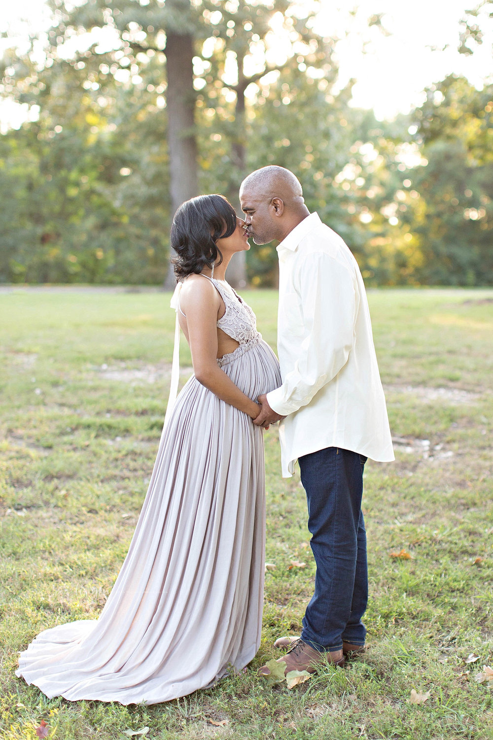 Image of a pregnant, African American woman, and her husband, facing each other, holding hands and kissing.