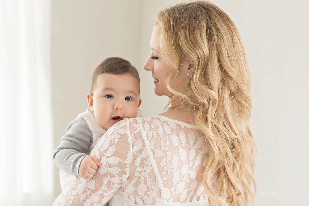 Image of a mother, in a cream lace top dress, holding her son on her shoulder while he looks at the camera.