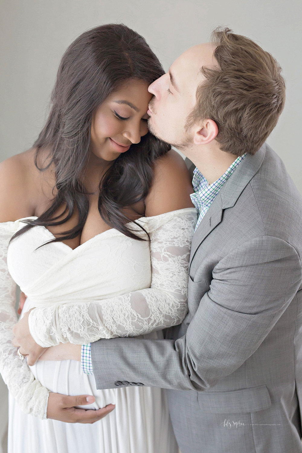 Image of an African American, pregnant, woman, wearing an off the shoulder, cream dress with lace sleeves, looking down and smiling, while her Caucasain husband kisses her forehead.