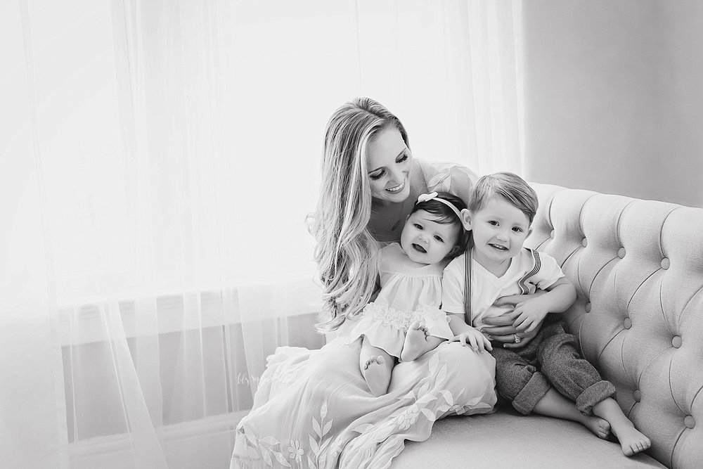 Black and white image of a mother sitting on a couch,smiling down at her baby girl and her toddler son sitting in her lap.