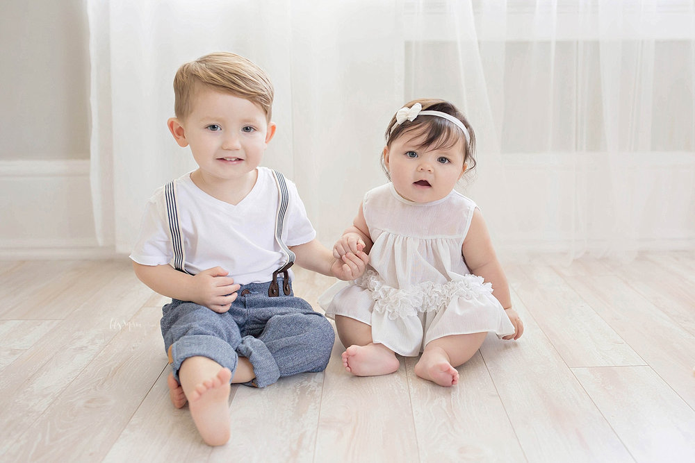 Image of a toddler boy in rolled up jeans and suspenders, sitting on the floor and holding his baby sister's hand.