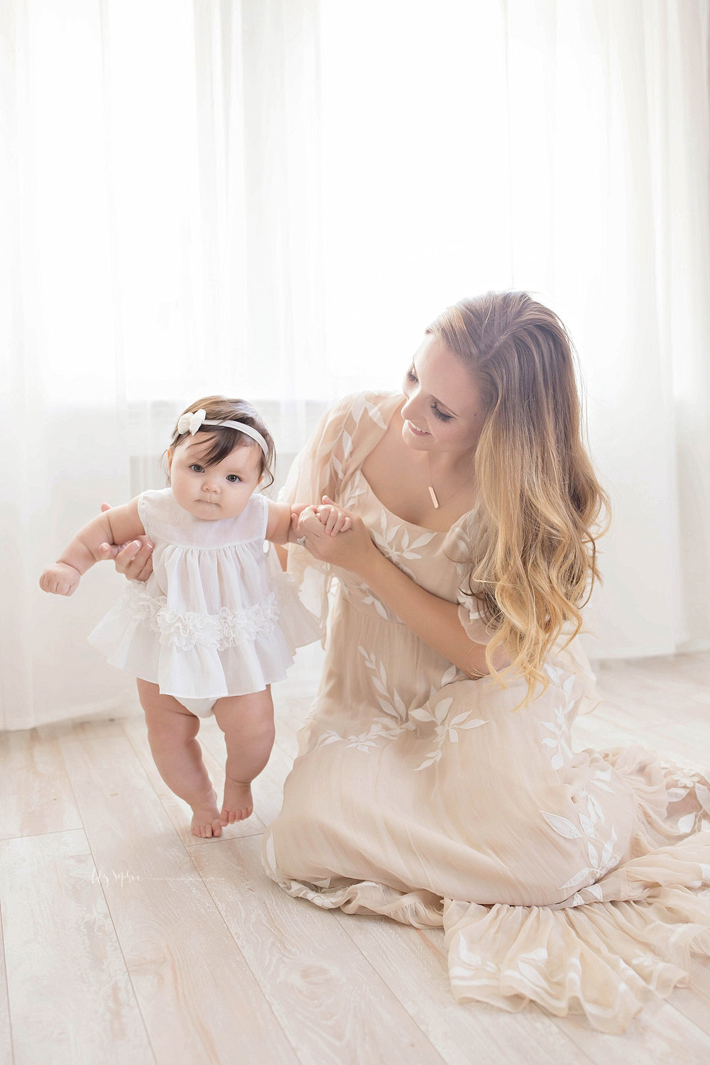 Image of a mother, wearing a taupe dress, helping her baby girl stand up.