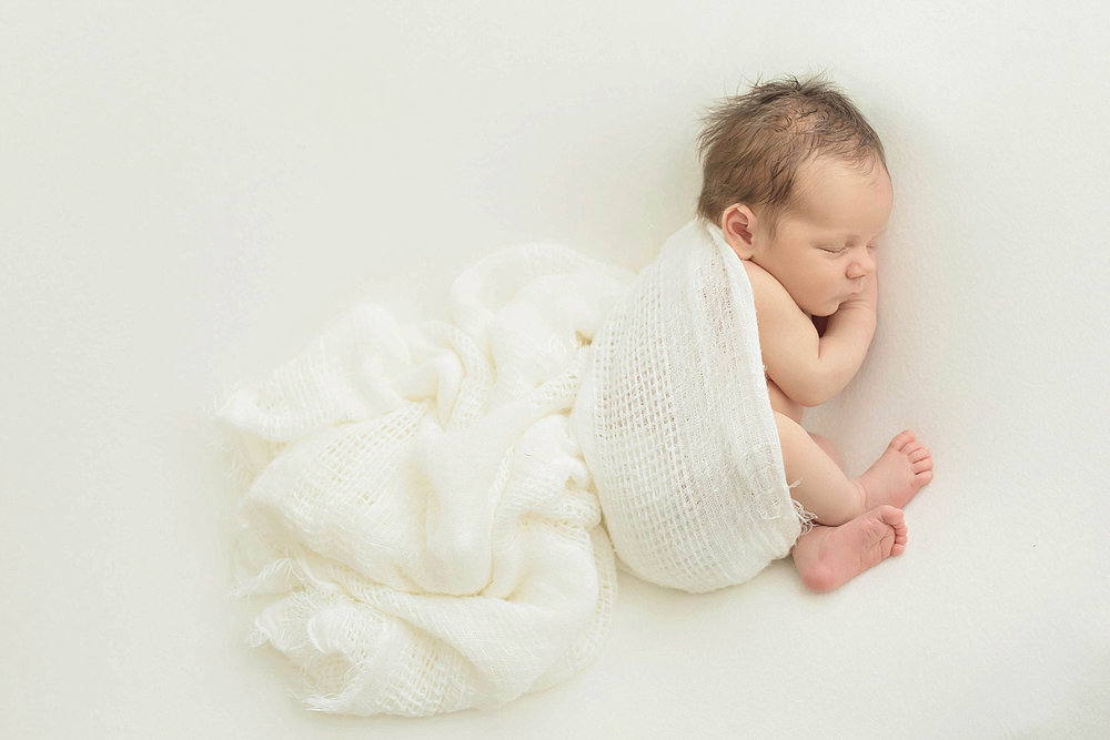 Image of a baby, newborn, boy, sleeping on his side, partially wrapped up in a cream blanket.
