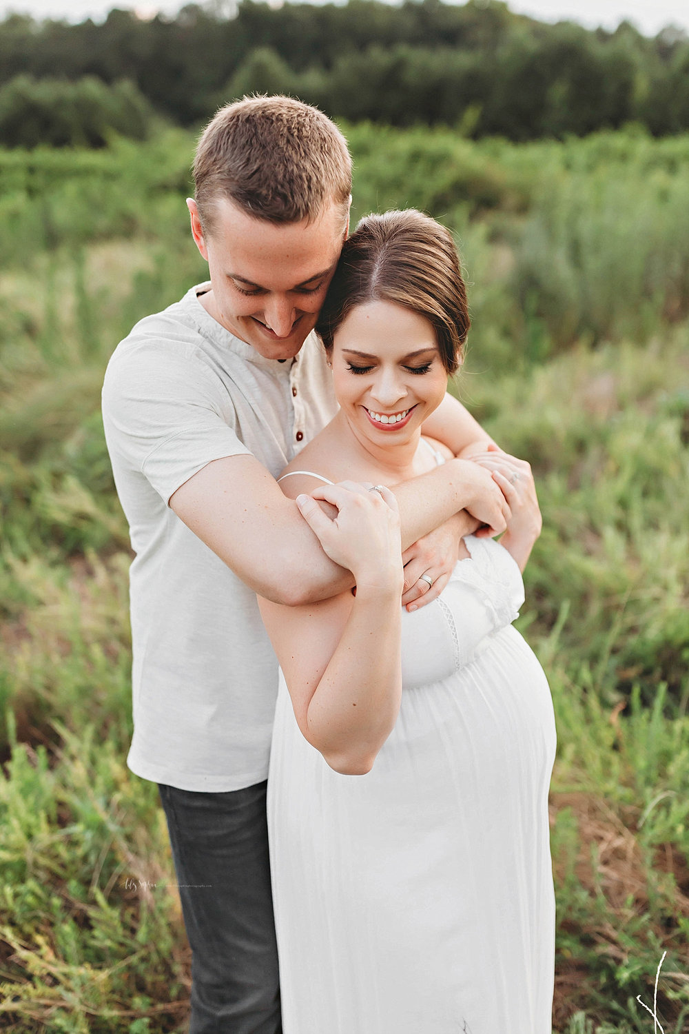 Image of a pregnant woman, wearing a spaghetti strap, white dress, while her husband wraps his arms around her neck.