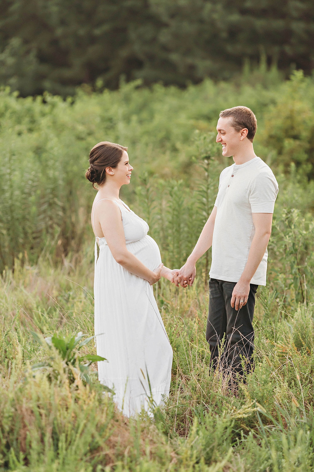 Image of a pregnant woman, and her husband, standing in a field, facing each other and holding hands.