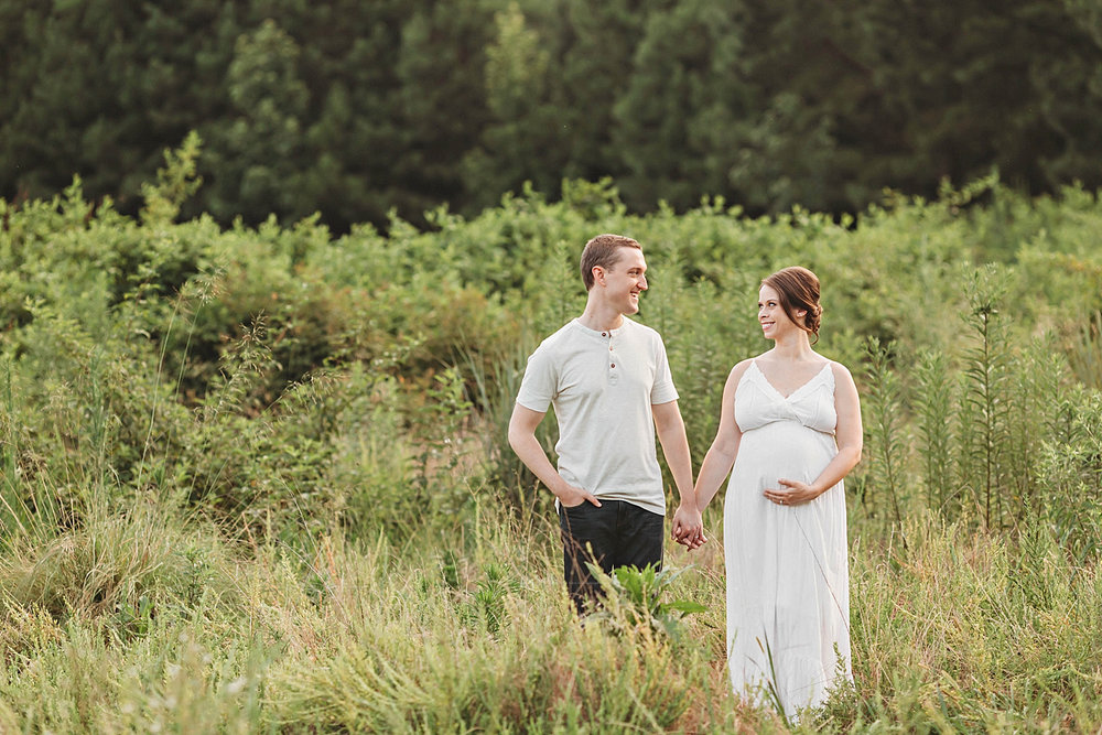 Side by side images of a pregnant couple, holding hands, and smiling at each other, in a field.