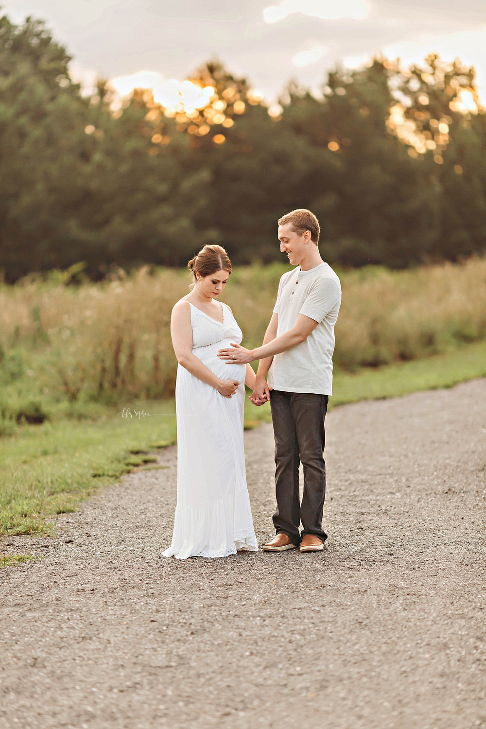 Image of a man, placing his hand on his wife's pregnant belly, while they are standing on a gravel path in a field.