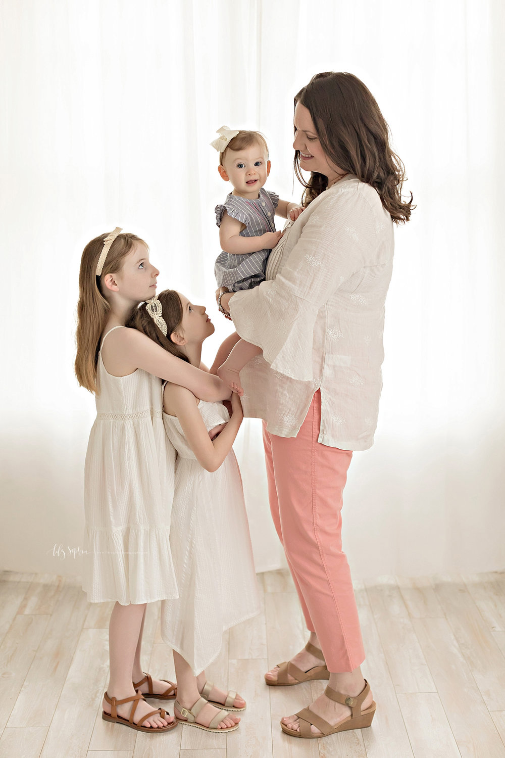 Image of a mother, wearing a long sleeved, cream dress, holding her baby daughter in her arms white her two older daughters look at her and she smiles down at them.