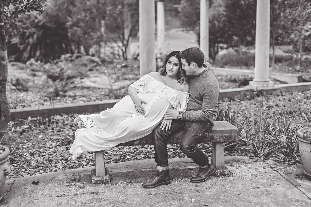 Black and white image of a man sitting on a stone bench, smiling down at his pregnant wife leans on him and has one hand on her belly.