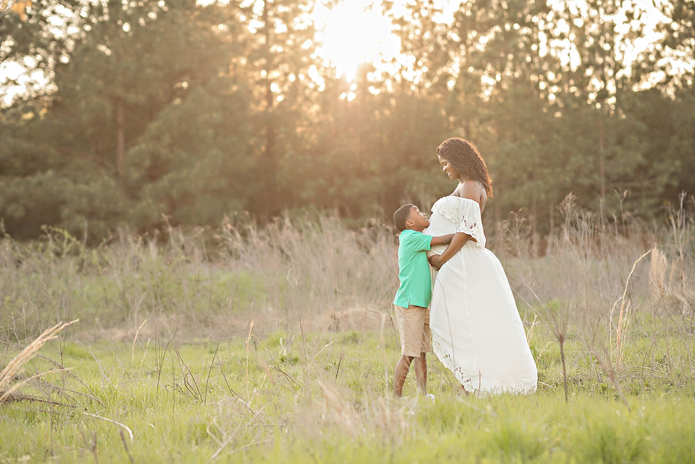 Image of a pregnant, African American, woman, standing in a field at sunset, hugging her son, while they look at each other and smile.