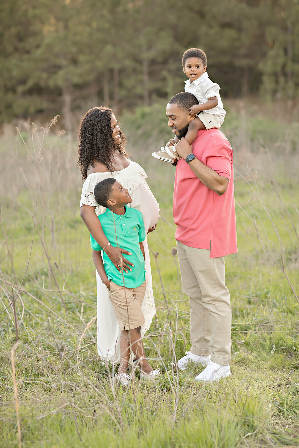 Image of an African American family of four, the mother has one arm around her 7 year old son and one hand on her belly, the dad has their toddler son on his shoulders.