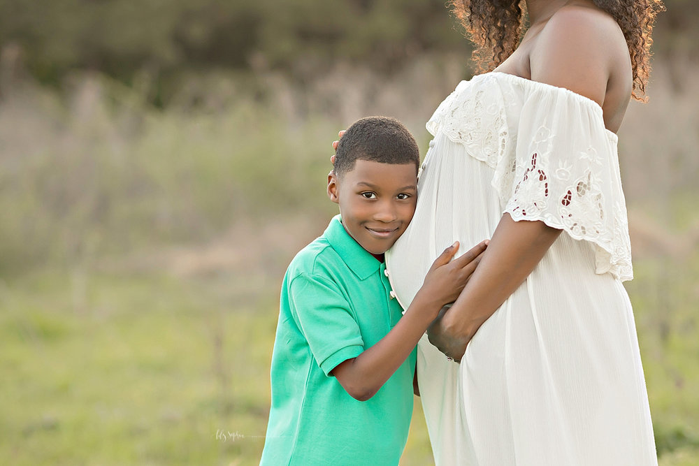 Image of an African American boy, grinning at the camera while he rests his head on his mom's pregnant belly.