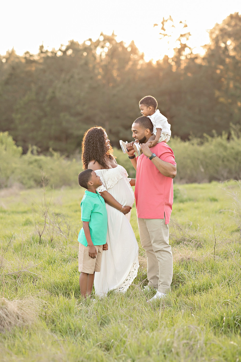 Image of a pregnant African American couple, with their two boys, standing in a field, smiling at each at sunset.